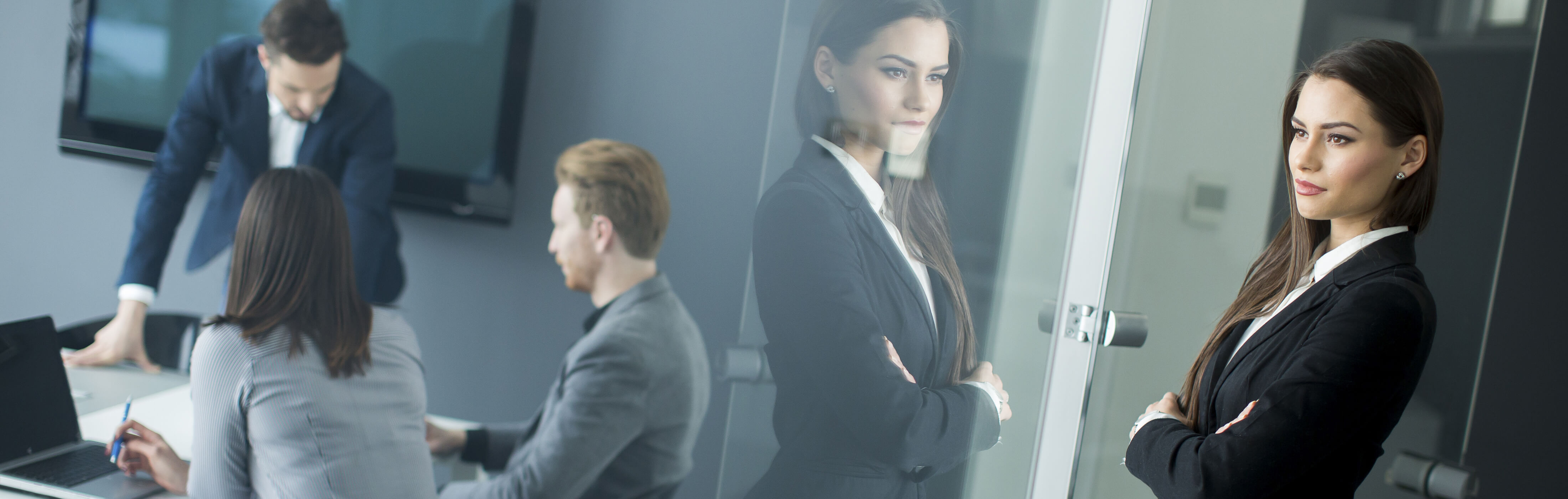 Attractive female manager watching her team through glass office wall, banner at the top of InnoScale Hosting's Server Management Packages page